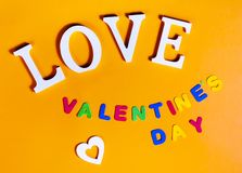 Word love in white, white heart and also colored words valentine`s day over orange background. Wood, love, background, colored, white, colors, heart, holiday stock photos