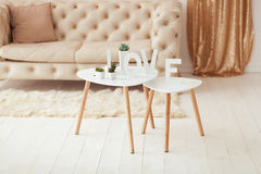The word Love in white letters on the interior volume background. Beige white sofa and coffee table in the room Royalty Free Stock Photos