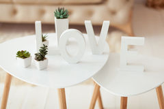 The word Love in white letters on the interior volume background. Beige white sofa and coffee table in the room Royalty Free Stock Photography