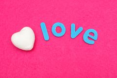 The word love with a white polystyrene heart. Isolated on a pink background Stock Images