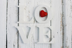 The word love on a white table. Word love with red heart on white wooden table table Royalty Free Stock Image