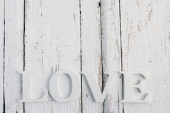 The word love on a white table. Word love with red heart on white wooden table table Royalty Free Stock Photography