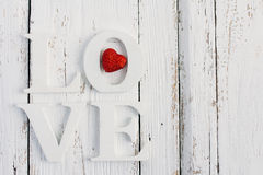 The word love on a white table. Word love with red heart on white wooden table table Stock Image
