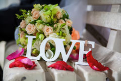 The word love in white wood and flowers Royalty Free Stock Image