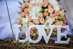 The word love in white wood and flowers Royalty Free Stock Images
