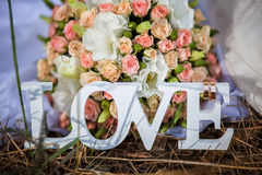 The word love in white wood and flowers Stock Photography