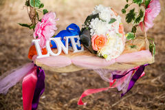The word love in white wood and flowers Stock Photos