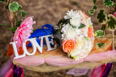 The word love in white wood and flowers Royalty Free Stock Photo