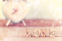 Word Love  on wood table with heart alarm clock, Royalty Free Stock Image