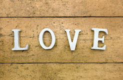Word LOVE on wooden background. Letters spelling `love` on wooden textured background. Old wooden floorboards are the background letters are colored white and in royalty free stock photography