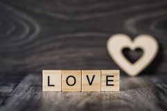 The word love from wooden cubes and a heart on dark woode. The word love from wooden cubes and a wooden heart on dark wooden background Stock Photos