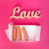 Word love, wooden letters on pink paper with fresh cupcakes. Valentine`s day background. Top view. Lovestory or wedding Royalty Free Stock Images
