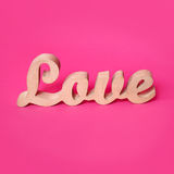 Word love, wooden letters on pink paper. Valentine& x27;s day background. Lovestory or wedding decor. Royalty Free Stock Photography