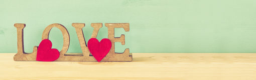 Word LOVE from wooden letters and red hearts Royalty Free Stock Images