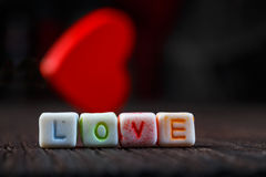 Word Love written in ceramic blocks with out of focus heart Royalty Free Stock Images