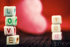 Word Love written in ceramic blocks with out of focus heart Royalty Free Stock Photography