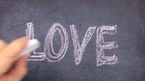 Word love, written with chalk on blackboard. stock video footage