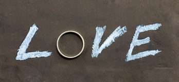 The word love written on chalkboard with a letter replaced with a ring. The word love written on chalkboard with a letter replaced with a silver ring stock photo