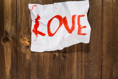 The word love written on the crumpled standard sheet which is pu Royalty Free Stock Photos