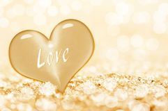 Word love written on a gold heart, shiny background. Word love written on a golden heart, shiny background stock images