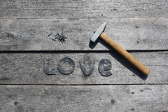 Word LOVE written by Metal nails. On wooden background royalty free stock photography