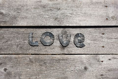 Word LOVE written by metal nails. On wooden background royalty free stock photo