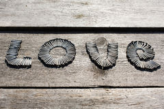 Word LOVE written by metal nails. On wooden background stock photos