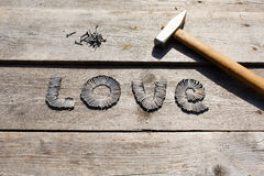 Word LOVE written by metal nails. On wooden background stock photography