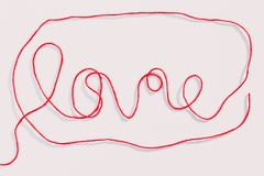 Word love written with red wool thread on white. Background. Horizontal view stock photos
