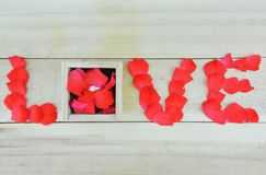 Word love written with rose petals and box with single stone rin Stock Photos