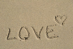 The word Love written in the sand. Beach with the word Love written in the sand Royalty Free Stock Photo