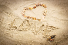 Word love written on sand at the beach, heart of shells Royalty Free Stock Photos
