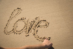 The word love written in the sand Stock Photography