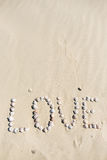 Word love written on the sand with sea shells at sunset on the beach Stock Images