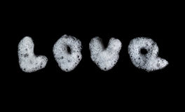 Word Love written soap foam bubbles. Figure lather, suds, shower texture and pattern. Black background. soft focus Royalty Free Stock Photography
