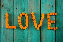 Word Love written by sweet bright pumpkin cubes on turquoise bac Royalty Free Stock Photography