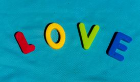 The word Love written by toy letters. The words composed from colorful children toy big letters of alphabet on the bright background. The word Love Royalty Free Stock Photo