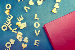 The word love written with wooden letters on a blue background. Red notebook. Royalty Free Stock Photography