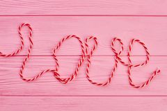 Word love written with woollen thread. Text love on pink wooden background. Love and romance concept Stock Photo