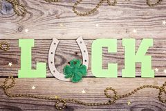 Word Luck with horseshoe and clover leaves on old wooden background. royalty free stock photos
