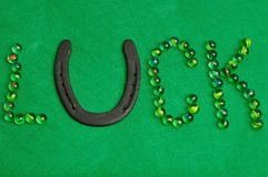 The word luck spelled with marbles and a horse shoe Stock Photography