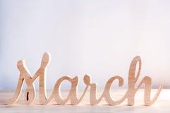 Word maand van MAART in hout met lichte achtergrond wordt gesneden die Begin van de lente De lente hello concept Royalty-vrije Stock Afbeeldingen