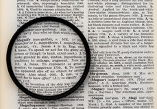 Word Magnify on a Dictionary Page viewed through a Lens. The word magnify on a dictionary page with its definition enlarged through a magnifying lens stock image