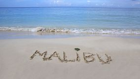 Beach of Malibu. The word Malibu written on the sand by the ocean Stock Photography