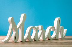 The word march carved of wood at blue background. Spring beginning concept.  Stock Images