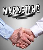 Marketing concept with a handshake. The word marketing above a handshake on grey background royalty free stock image