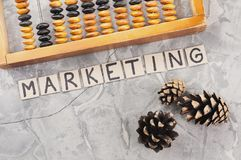 Word MARKETING laid out of handwritten letters on cardboard squares near old wooden abacus and three cones. On gray cracked concrete royalty free stock image