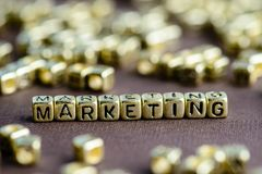 Word MARKETING made from small golden letters on the brown backg. Round, selective focus. Business concept background royalty free stock image