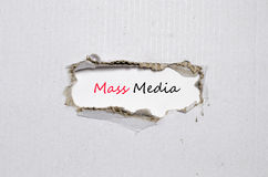 The word mass media appearing behind torn paper. The word mass media behind torn paper stock image