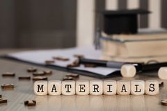 Word MATERIALS composed of wooden dices. Black graduate hat and books in the background. Closeup stock image